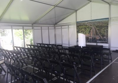 Road Opening - VIP marquee with black folding chairs and stage