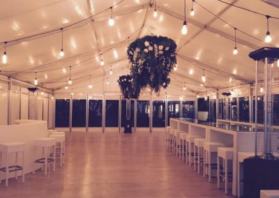 VIP Marquee with whitewashed vinyl floorboards and white rattan